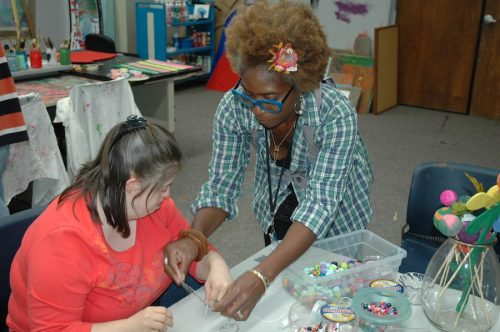 Woman helping artist try on bead bracelet