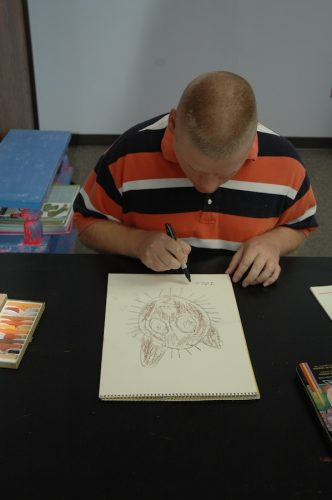 Artist signing cat drawing