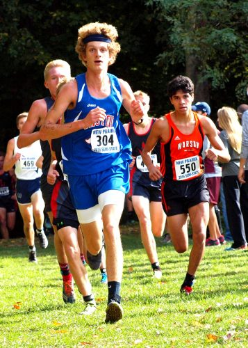 Warsaw sophomore Zeb Hernandez (550, right) chases eventual champ Mitchell Rans of Caston (304) out of the woods near the 3,000-meter mark during the boys cross country semistate Saturday at New Prairie. Rans and Hernandez finished 1-2. (Photos by Tim Creason)