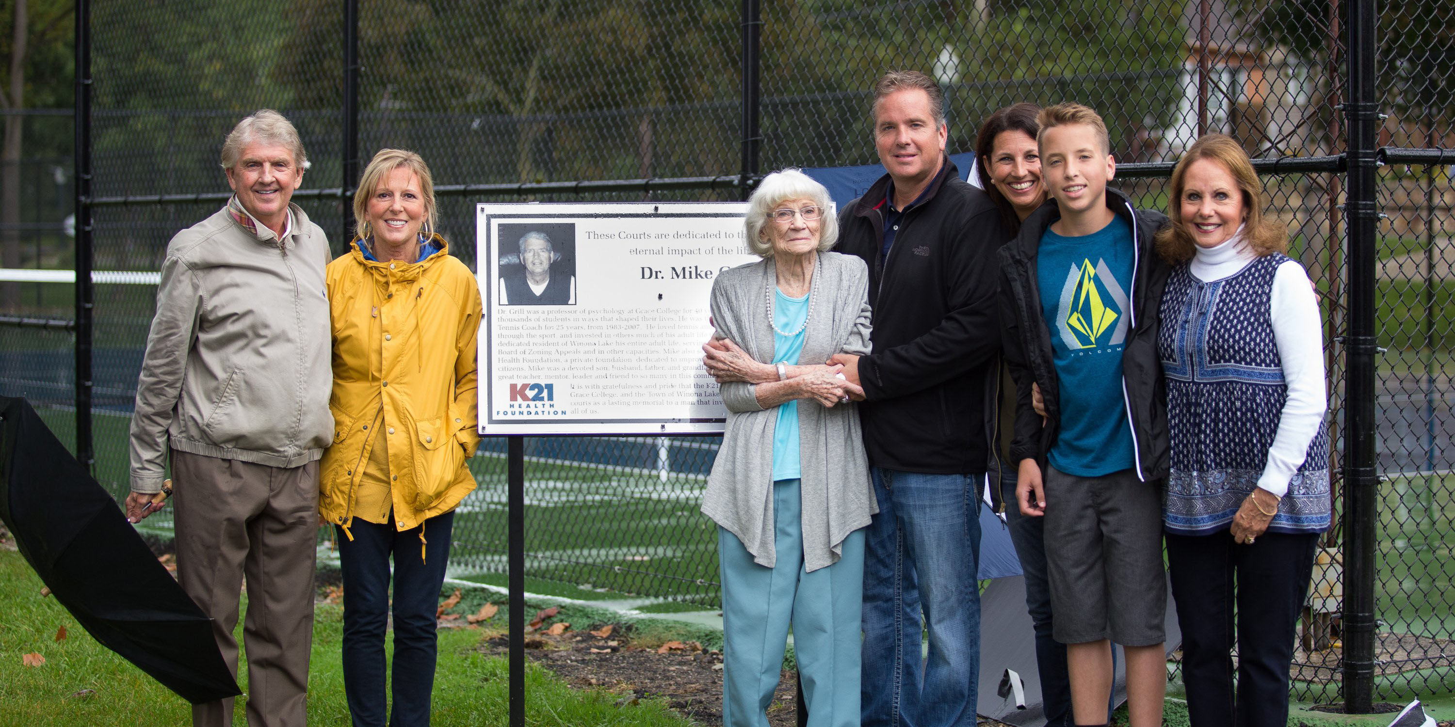 Steve, Susan, Kittie, Josh, Amy, Ethan and Becky Grill next to the Dr. Mike Grill Memorial Courts plaque.
