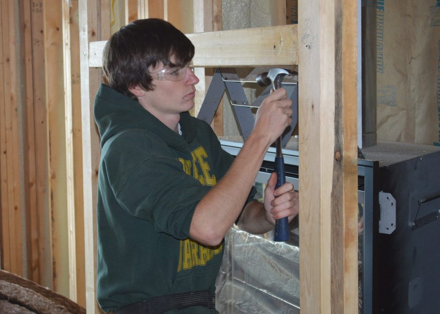 Wawasee student Samuel Griner works on the framing around the fireplace.