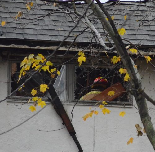 A firefighter in the upstairs area of the residence after being called back to the home Friday morning.