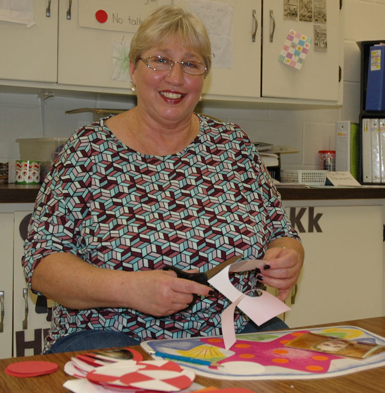 Connie Anderson sits cutting out crafts her preschool and 3-year-old students will work on throughout the holiday season at Pierceton Presbyterian Church.