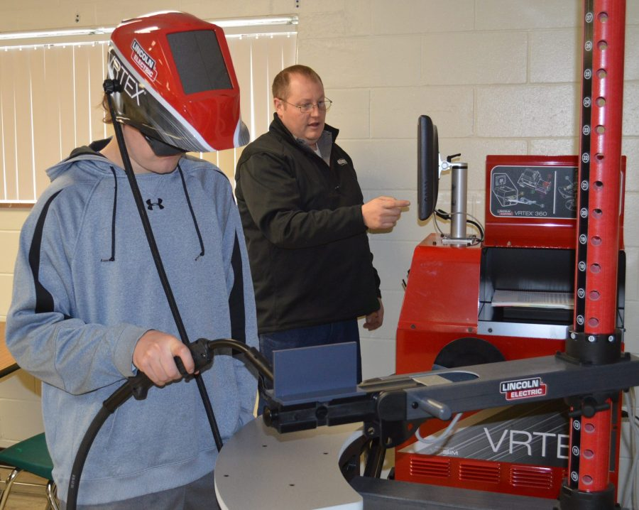 Dominic Richardson, Wawasee High School student, uses the virtual welder while in the background instructor Jesse Kimmel monitors the computer screen.