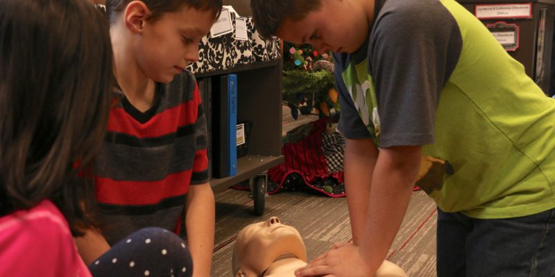 Lucas Wagner practices compressions on a CPR mannequin