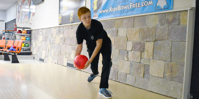 Mikey Cox bowling with a two-handed approach.